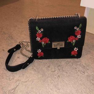 Sötaste väskan i svart mocka (imitation) med broderade rosor i rött! Från Pull & Bear. Silvrigt axelband i kedja med läder vid axeln, så den är bekväm! Frakt tillkommer🥰