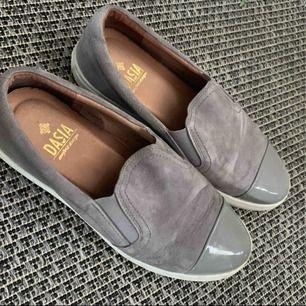Ett par skor som användes förut men inte längre! Dem är fortfarande i bra skick och är i en ljusgrå mocka färg med glans längst fram