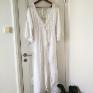 Vacker vit klänning, V-ringning fram och bak. Använd två ggr. Miniminifläck som kan ses på tredje bilden.