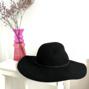 Svart hatt med ganska stor skärm, rundad på huvudet 🌼