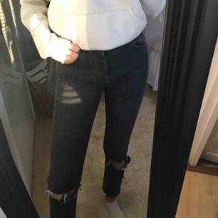 Ett par mom jeans med hål i knäna samt avklippta vid anklarna med lite tajtare modell från bikbok, i en mörkgrå färg med knappar som gylf. Använda ca 2 ggr, är stretchiga i tyget🥰 (kunden står för frakt)