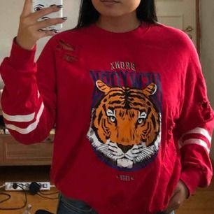 Röd sweatshirt från Gina Tricot med lite hål på