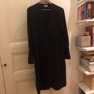 Svart långärmad klänning / tunika från Weekday. I skirt material, fin till jeans eller bara som klänning. Knäpps framtill samt slitsar på sidorna. Kan skickas mot fraktkostnad eller mötas upp i Stockholm.