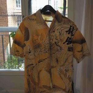 En kortärmad skjorta i storlek M som är inköpt i London på second hand-butik. Väldigt snyggt kinesiskt draktryck över hela skjortan.