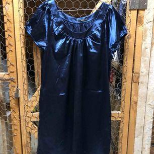 Blå glättig klänning som ser helg oanvänd ut.