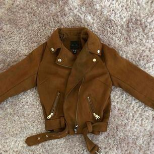 Skitsnygg brun mockajacka i bikermodell från märket New Look i stl S. Aldrig använd.