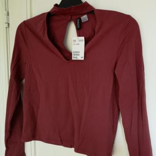 En mörkröd fin tröja med öppning vid brösten och liten öppning vid ryggen. Även en