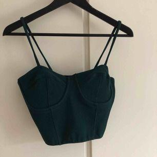 """Snyggt linne i mörkgrön färg, med """"BH"""" på utsidan,i kort modell"""