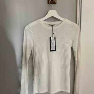 Vit långärmad tröja i ribbat material. Storlek XS. Passar även S. Helt ny med prislapp. Aldrig kommit till användning! Nypris 259kr :)