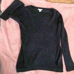 Stickad tröja som glittrar, har sidoöppningar och är lång där bak och kortare där framme!