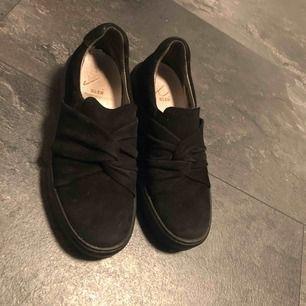 Hel svarta mocka lågskor med en knut på. Köpta förra året men använda cirka 10 gånger. Jättefina och kan styla upp en outfit. De står att de är 35 men de kan finns utrymme för storlek 36.