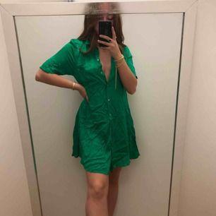 Superfin grön klänning i satinaktigt tyg. Använd 2ggr. Säljer för använder den så sällan. Vill man ha tajtare i midjan så är den superfin med ett skärp som jag håller med handen på första bilden. Frakt ingår i priset✨