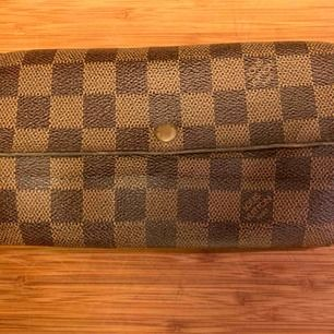 Vintage Louis Vuitton Plånbok. Skick utger du själv utifrån bilderna. Knappen funkar inte. Vid behov av fler bilder eller frågor skicka Pm Datecoden är: SD0075 Måtten är:18,5x10,5cm Köparen står för frakt