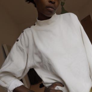 Cremevit sweater med nicea detaljer och höghals. Lappen är bortklippd, köpt på second hand. I bra skick, lätt och skön att bära.