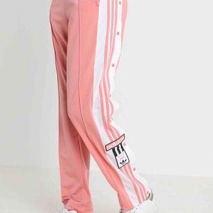 Adidasbyxor, ljusrosa, slit med knappar och fickor. Använda endast en gång pga inte min stil.
