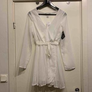 •vit klänning med delvis tyll •reglerbart band i midja •resår midja •transparent ärm •oanvänd med prislapp kvar