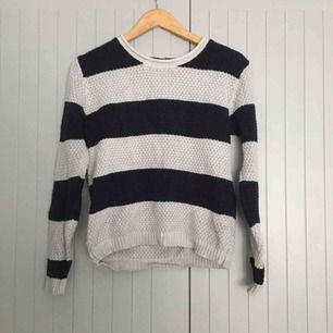 En stickad, vit och mörkblå-randig tröja i storlek S. Använd 2-3 gånger. Storlek S. Det är mörkblå men eftersom den är såpass mörk så ser den ut att vara mer svart. Finns på flera sidor.