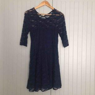 Mörkblå spetsklänning i storlek M. Stretchigt material.