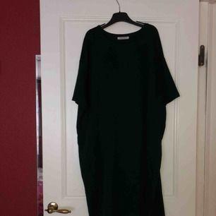 En lång oversize tröja. Mörkgrön. Den blir som en klänning på mig och går ner till mina knän ungefär och jag är 162 cm. Den ser också fläckig ut på ena tredje bilden men är ej det. Det är ljuset i bilden.