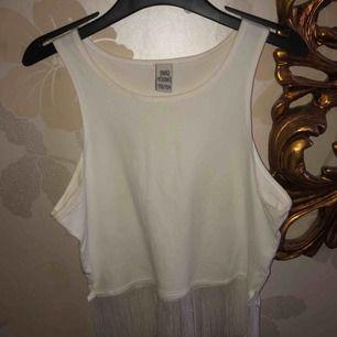 En tröja jag köpte för länge länge sedan på Ullared. Den passar säkert den som har storlek XS, möjligtvis S. En vit croptop med fransar längst ner.