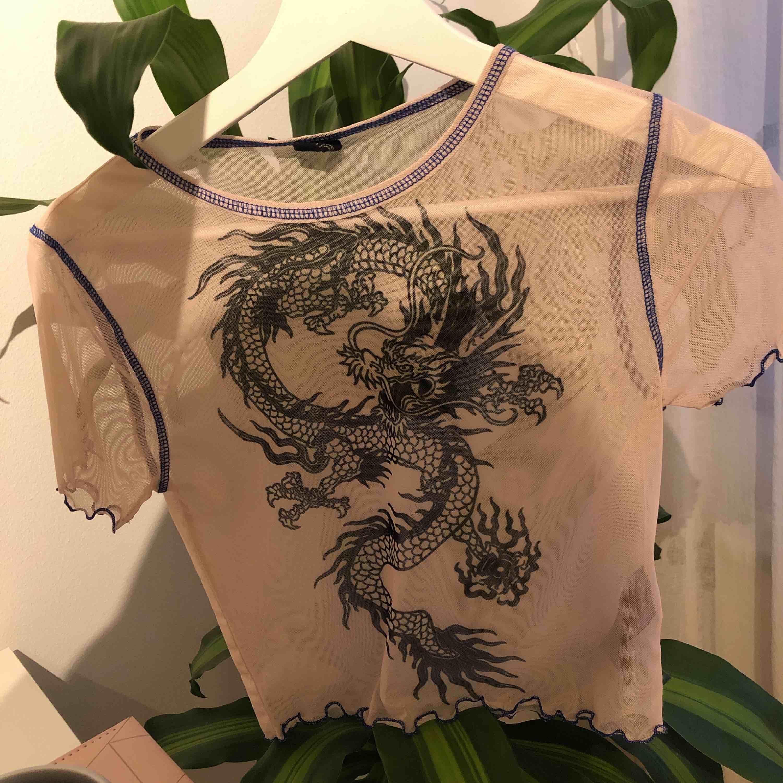 Beige genomskinlig tröja i strl s, med ett svart drack tryck i mitten. Den är ifrån Urban Outfitters och använd någon fåtal gång. Köparen står för frakt, men kan mötas upp i Stockholm!. Toppar.