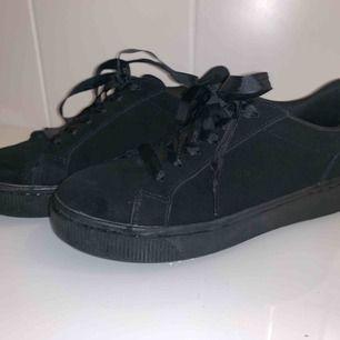 Svarta sneakers i mocka-immitation. De är blöta på sulan för jag precis tvättade av dem