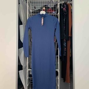 Lång klänning i ribbat material från BOOHOO. Snygg blå färg. HELT ny med prislapp. Slits på vänster sida längst ner samt turtleneck. Stretchigt material. Passar mig som har XS/S. Kan skicka bild med den på om så önskas!