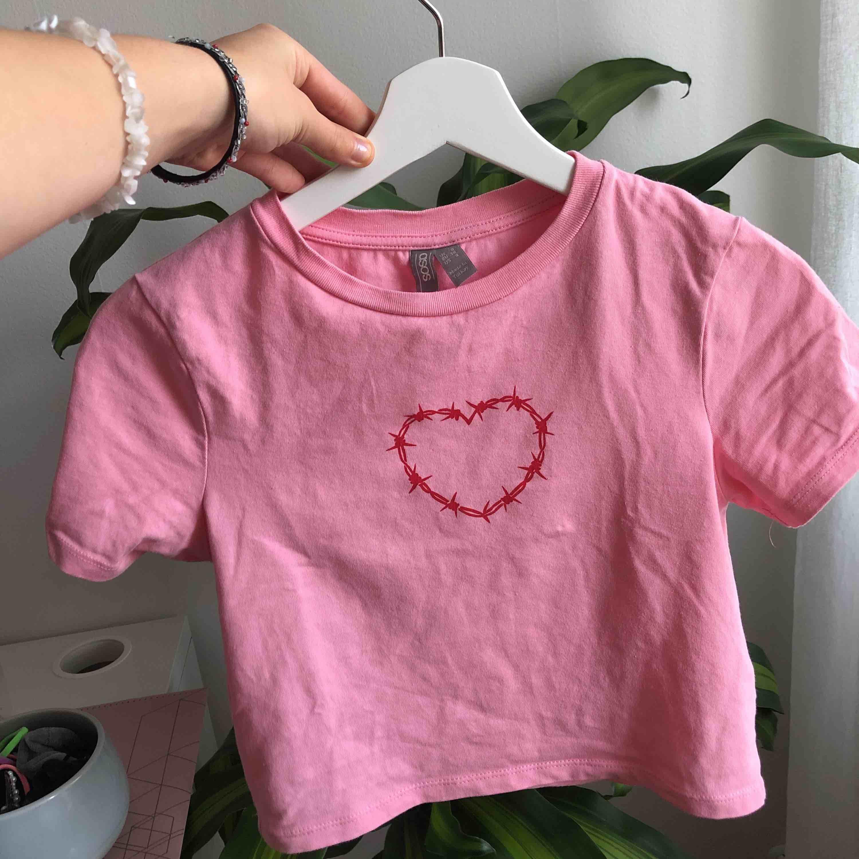 Rosa tröja med ett rött hjärta på, från ASOS. Använd ett fåtal gånger. Köparen står för frakten, men kan även mötas upp i Stockholm!💖💗🌸🍀. Toppar.