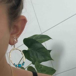 Ett par guldiga örhängen med fem turkosa stenar. Eller ett par guldiga örhängen med fem mörklila stenar. Gör självklart rent dem med alsolsprit innan jag säljer dem! De kostar 100kr var!