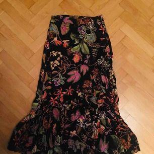 Poppis kjol till salu! Köpte fel storlek så har haft den en gång bara. Volanger och vackert tryck! Figurnära.