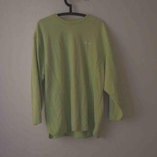 En sportig, långärmad sweatshirt med Adidas-logotyp i lower case. Rave/Neon-tappad stil, med mesh-syning.