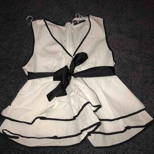 Fin vit blus från Zara med svarta detaljer och en svart rosett man knyter där fram eller bak, beror på vad man själv tycker om