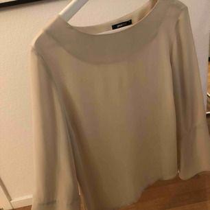 Beige blus med utsvängda armar, använd några gånger men inte använt den på flera månader. Har endast hängt i garderoben. Köparen står för frakt.