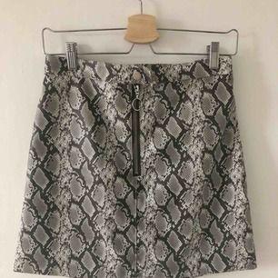 Kort kjol från hm i snakeprint i storlek 38, frakt tillkommer
