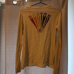 Härlig långärmad beige t-shirt från Burton med tryck på rygg samt vänster arm