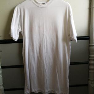 En vit t-shirtklänning med tryck på ryggen. Använd ett fåtal gånger, fortfarande helt vit.   Passform: avslappnad/oversize  Längd: 81 cm Material: 100% bomull