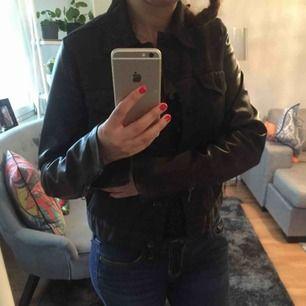 Tiger of Sweden jeans jacka i svart färg , armarna är i läder .