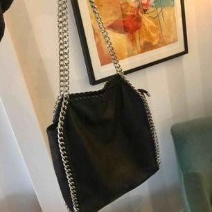 Svart väska med silver detaljer i mycket bra skick! Har tre små fickor, en på utsidan och två på insidan!  Köparen står för frakten🌸