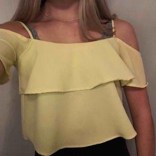 Gul off-shoulder tröja. Det går att ändra längd på banden.+frakt