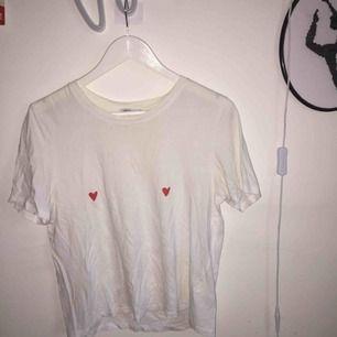 T-shirt från Monki med hjärtan över bröstvårtorna. Bra skick, liste skrynklig bara från att ha legat i min garderob, oanvänd.