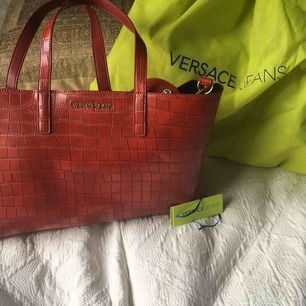 """En äkta Versace väska ( med authenticity tag)  i imitations läder knappt använd och med löstagbar bagstrap samt en """"inneväska"""" som går att ta bort"""