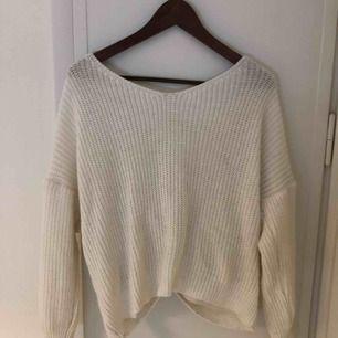 """Lite oversize vit stickad tröja med djup urringning i bak med pärlor och """"knut"""". Kan även användas med pärlorna framåt."""