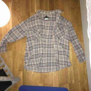 En beige-rutig skjorta av ganska tjockt material, så den kan användas som en tunn jacka över exempelvis en hoodie. Köpt på en secondhandbutik och är i väldigt fint skick. Passar allt från storlek XS till L.