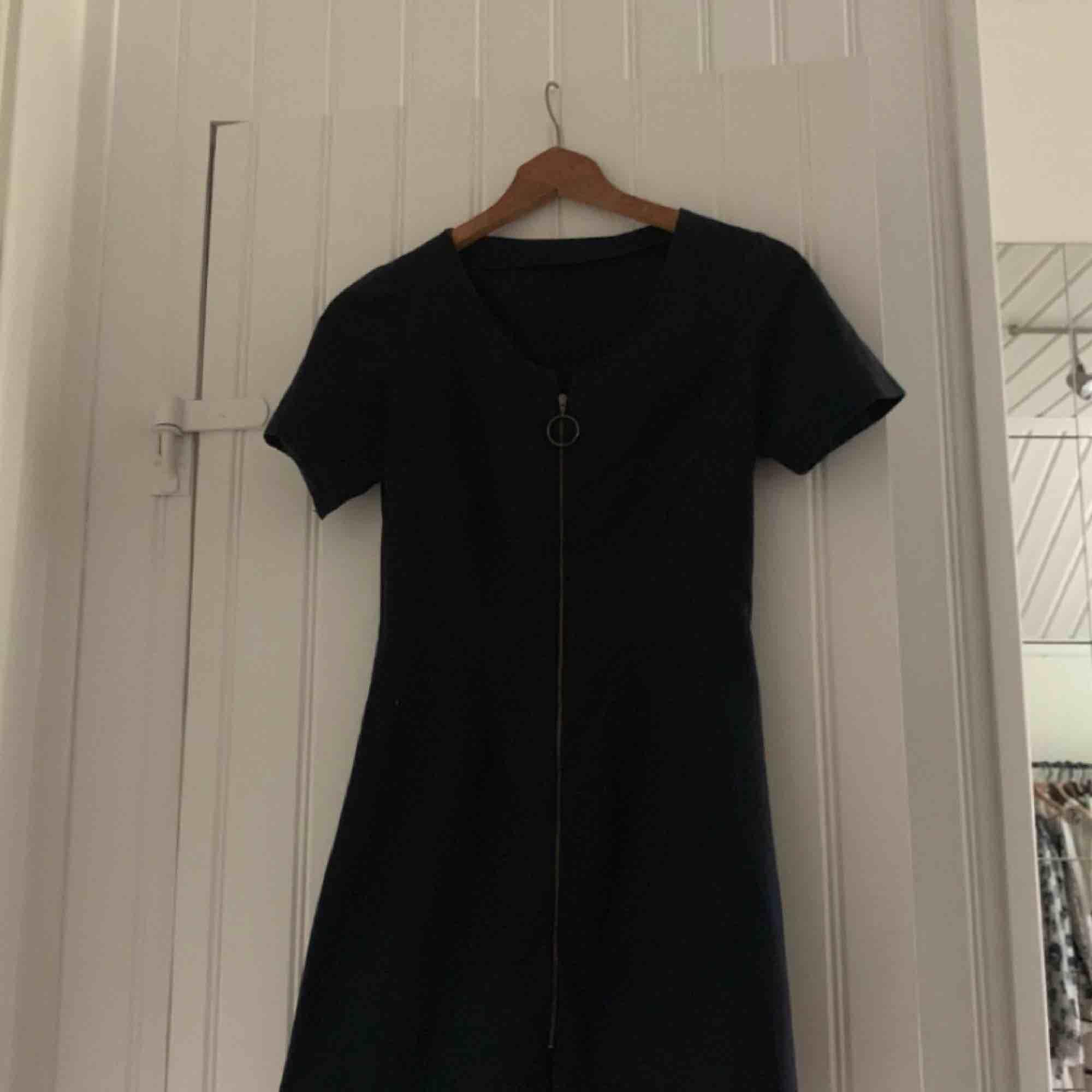 En svart klänning med en dragkedja som går att dra ner hela vägen. Inte i stretchmaterial. Storlek XS, passar även XXS tror jag:) köpt på second hand, men bara använd en gång av mig. Bra skick! Tveka inte att fråga något eller lägga ett bud!  . Klänningar.