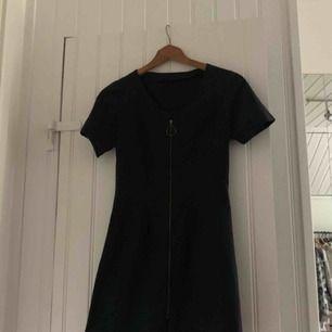 En svart klänning med en dragkedja som går att dra ner hela vägen. Inte i stretchmaterial. Storlek XS, passar även XXS tror jag:) köpt på second hand, men bara använd en gång av mig. Bra skick! Tveka inte att fråga något eller lägga ett bud!