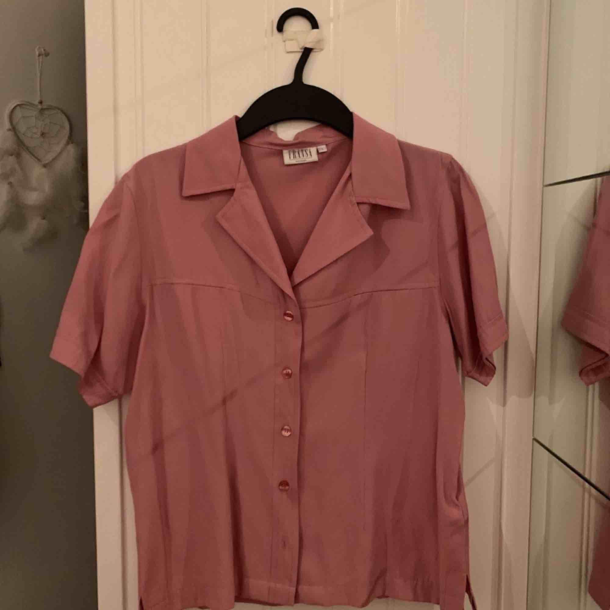 En rosa-lila blus/kortärmad skjorta i storlek S. Aldrig använd av mig, men köpt på second hand. Dock i nyskick. Tveka inte att ställa en fråga eller lägga ett bud!. Blusar.