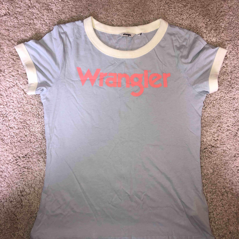 Ljusblå Wrangler tröja som användes några gånger en sommar!  Tar swish! Köparen betalar frakt och priset beror på vart du bor i Sverige!. T-shirts.