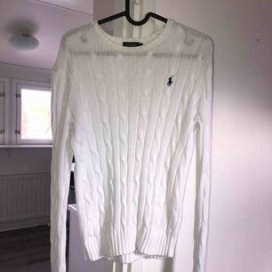 Vit Ralph Lauren kabelstickad tröja! Lite uttänjda armar pga tvätt och små foundation fläckar vid halsen, men borde gå bort i tvätten! Tar swish! Köparen betalar frakt och kostnaden beror på vart du bor i Sverige!