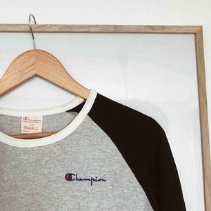 En långärmad t-shirt i svart och grått. Frakt tillkommer