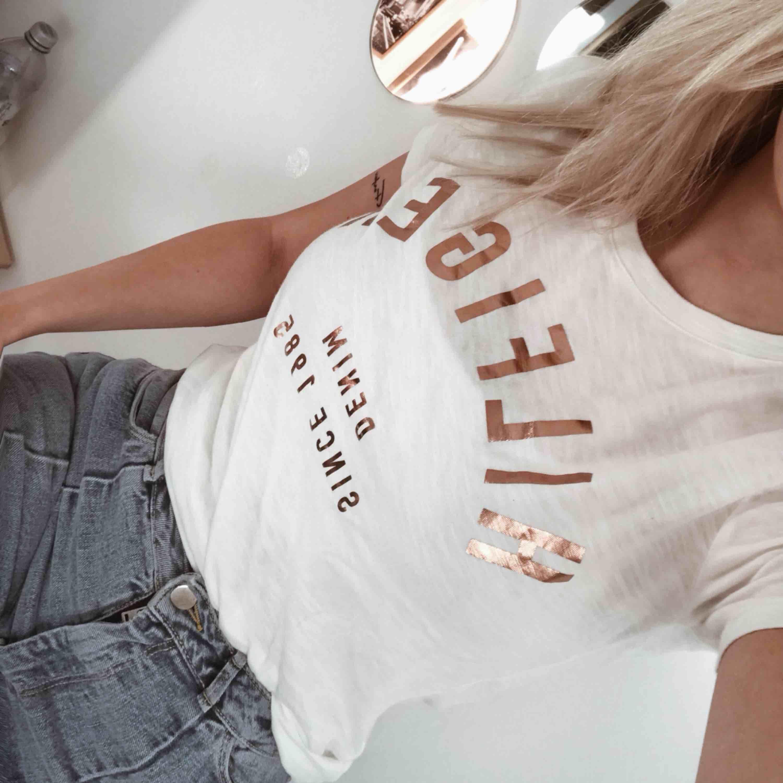En vit t-shirt med text i rose. frakt tillkommer . T-shirts.